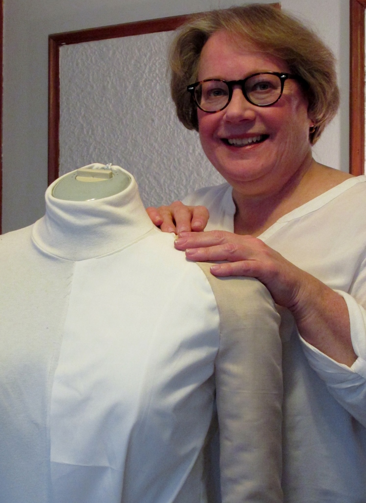 author standing at dress form with sample of raglan sleeve