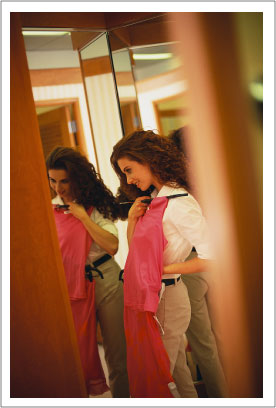 woman holding a dress while looking in a mirror